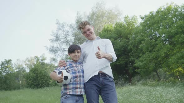 Thumbnail for Portrait Boy and His Dad Showing Thumbs Up. The Child Holding Soccer Ball Hugging with the Dad