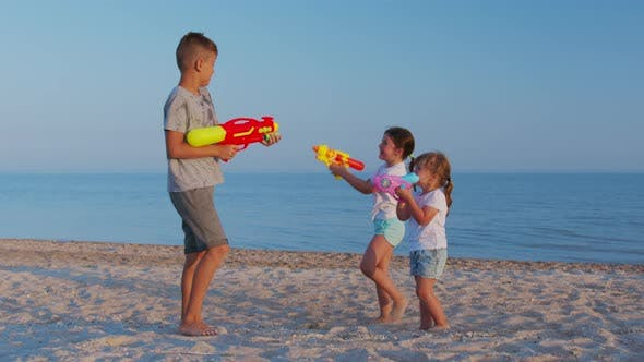Thumbnail for Little Girls and Boy on the Sea. Children Playing with Water Guns.