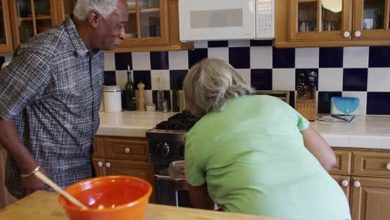 Mature black couple baking cookies