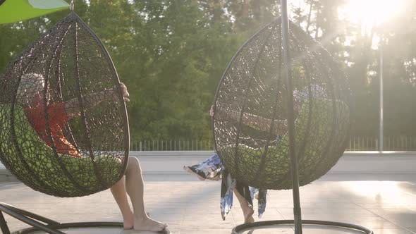 Thumbnail for Grandmother and Grandfather Resting Sitting on Hanging Chairs in the Sun