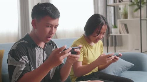 Asian Children Playing Video Games On Mobile Phone At Home