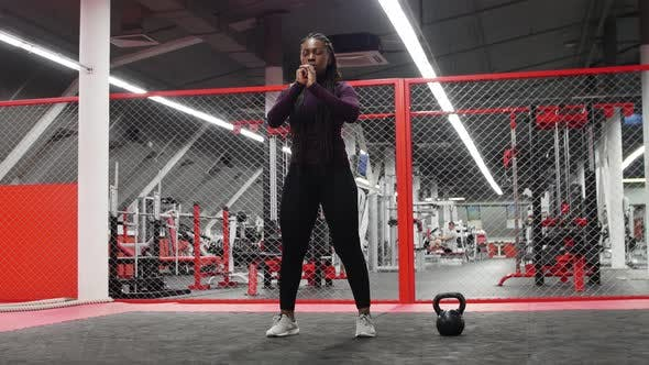 Sports in the Gym  Africanamerican Woman Squatting