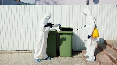 Sanitation doctors disinfect trash bins, garbage containers.