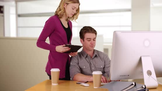 Female using touchpad device standing behind male colleague working on computer