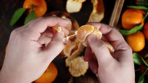Men Hands Divide the Tangerine Into Slices