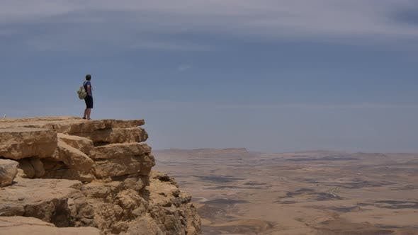 Thumbnail for Man with Backpack Standing on the Desert Mountain Rock Cliff Edge
