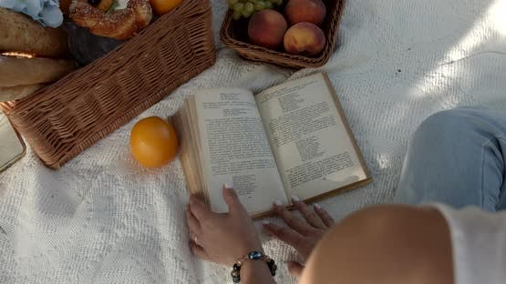 Girl Flips Through A Book On A Picnic In The Garden