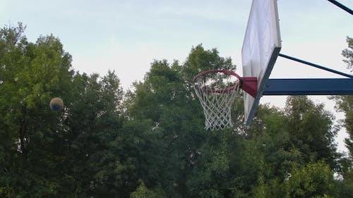 Junger Mann trainiert Springen mit Ball, um Ring zu schlagen. Basketballspieler spielen im Freien. Sport Motivation