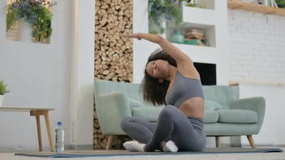 Young African Woman Doing Yoga on Yoga Mat at Home
