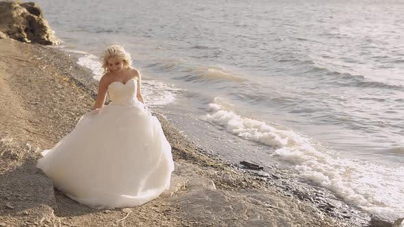 Thumbnail for Beautiful and Lovely Bride Walking Along the Coast of the Sea