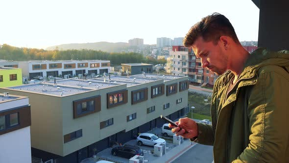 Thumbnail for A Young, Handsome Man Types on His Smartphone on a Balcony, Eventually Looks Out
