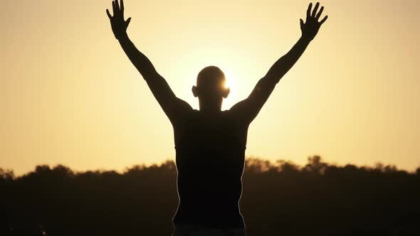 Thumbnail for Silhouette of Young Man Raising Hands To Sides and Up Against Sunset Slow Motion