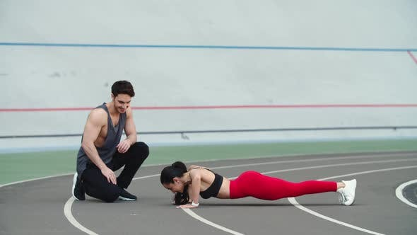 Thumbnail for Woman Doing Push Ups on Sport Stadium. Couple Training Together at Sport Stadium