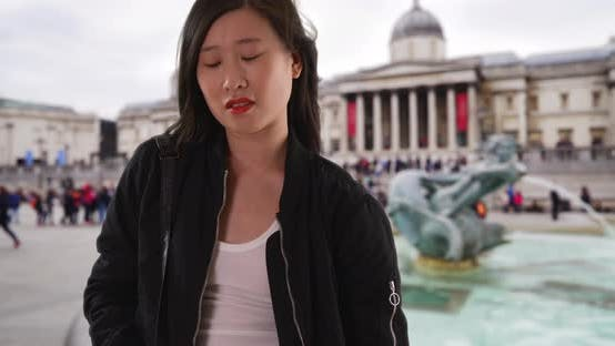 Thumbnail for Chinese woman in black bomber jacket with hands in pockets on holiday in London