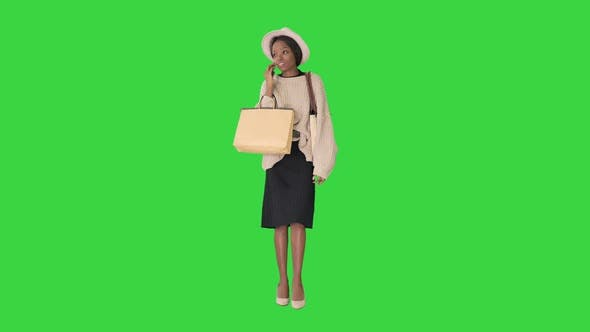 Thumbnail for African American Girl in Oversized Knitwear and Hat Talking on Her Phone While Walking with Shopping