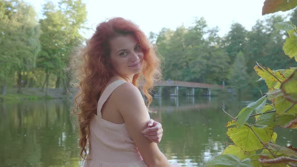 Thumbnail for Young Girl with Red Hair Turning To the Camera and Smiling. Pretty Caucasian Woman Sitting on the