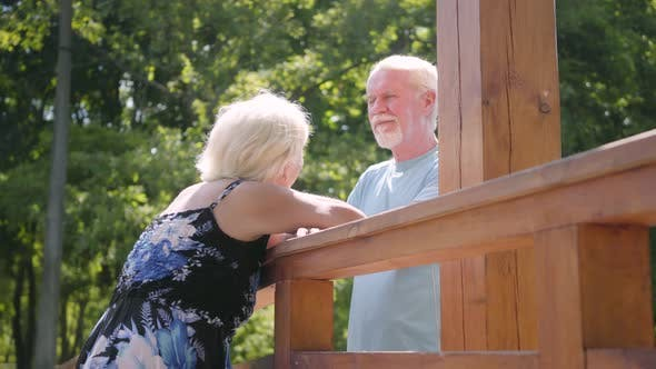Thumbnail for Happy Mature Couple Standing at the Bridge Talking and Smiling