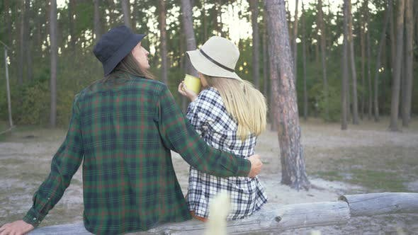 Thumbnail for Back View of Tourist Couple in Plaid Hipster Shirts and Hats Sitting in the Forest