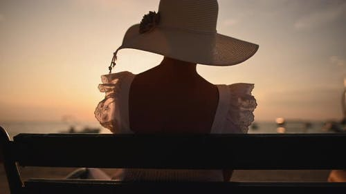 Back of Caucasian Woman in Hat Seating Face to Ocean