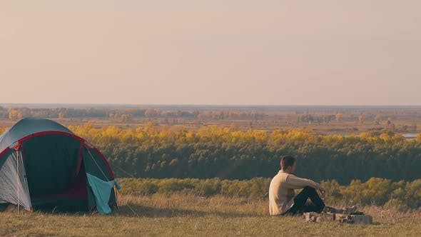 Thumbnail for Sad Guy Sits By Camp Bonfire and Looks at Autumn Forests