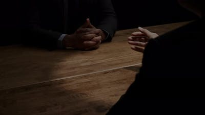 Businessman secretly giving money to his partner in the dark room