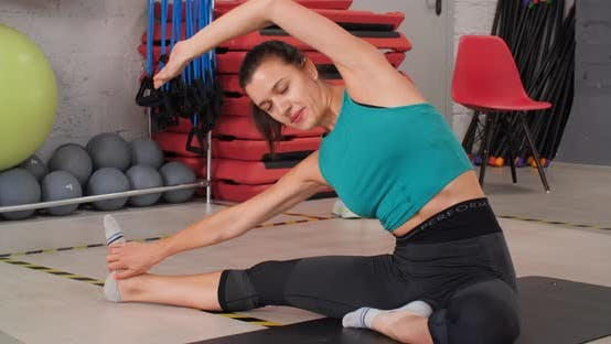 Happy Young Woman Stretching auf Matte im Fitnessstudio