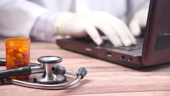Doctor Working on Laptop with Pills Container and Stethoscope on Table