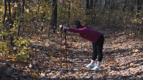 Thumbnail for Chubby woman stretching her back and hips before nordic walking training in autumn park