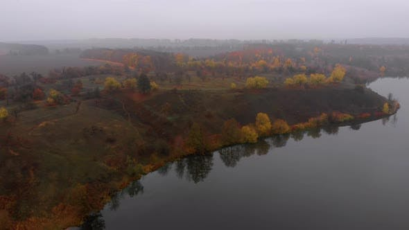 Aerial Drone Shot of Colorful Nature Near Big River in Fog at Late Autumn