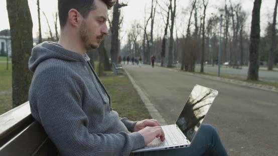 Thumbnail for Man using a laptop in the park