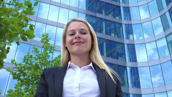 Cover Image for A Young Beautiful Businesswoman Smiles at the Camera - Closeup From Below - an Office Building