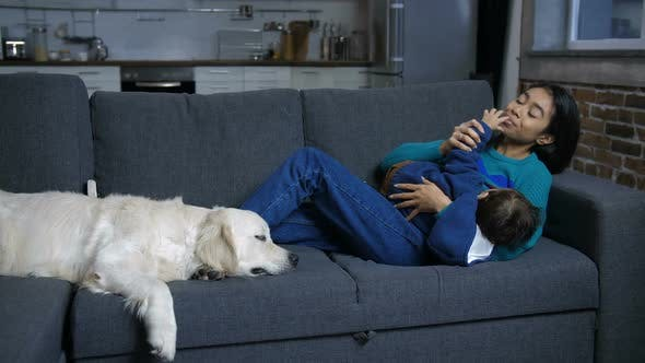 Thumbnail for Hindu Mom and Infant Relaxing on Sofa with Dog