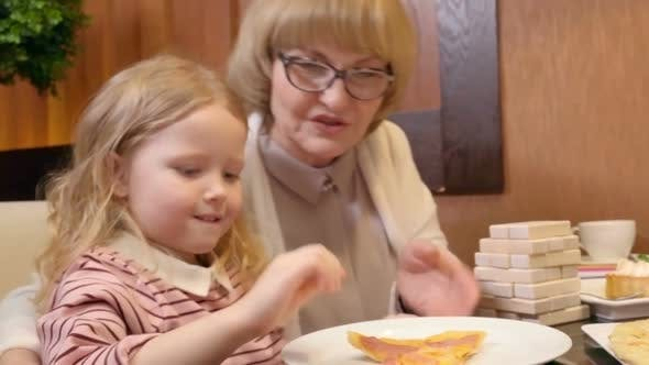 Thumbnail for Little Girl Having Pizza at Family Dinner in Cafe