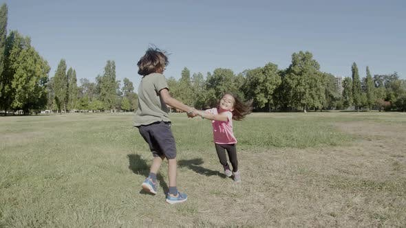 Long Shot of Happy Brother Circling Little Sister Around on Lawn