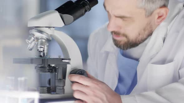 Thumbnail for Male Caucasian Researcher Peering into Microscope