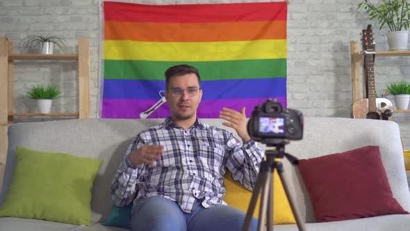 Portrait Man Blogger Mittlerer im Shirt auf dem Hintergrund der Flagge der LGBT Records Video