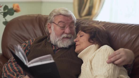 Thumbnail for Elderly Couple Sitting on the Cozy Sofa, Having a Pleasant Conversation, Nostalgic and Discussing