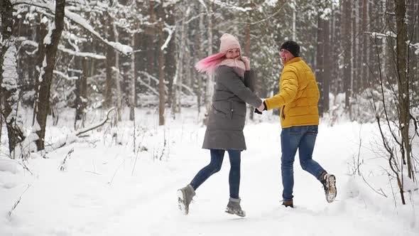Thumbnail for A Young and Beautiful Couple Is Having Fun in the Park, Running and Holding Hands. Valentine's Day