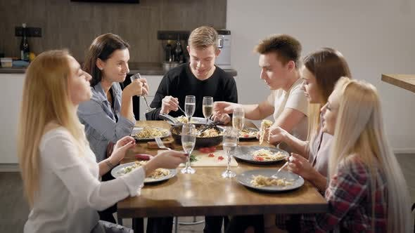 Thumbnail for Group of Young Roommates Are Sitting at Table and Dinning, Clicking By Wine Glasses Saying Toasts