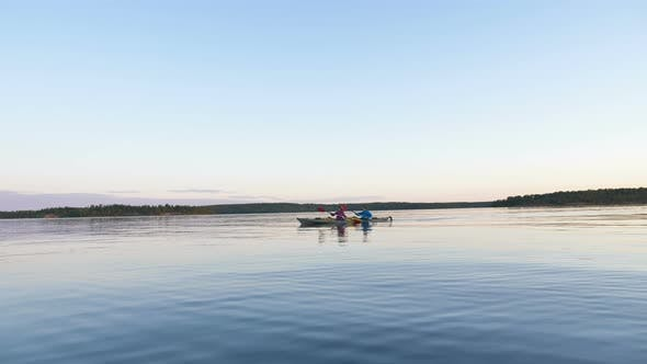 Thumbnail for Man and Woman Row Sports Kayak Along Large Tranquil River