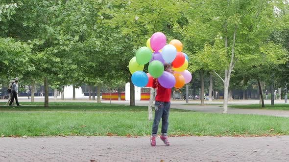 Thumbnail for Smiling Girl Playing with Multicolored Balloons, Slow Motion