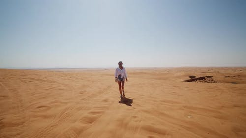 Front View of Young Woman in Sunglasses and Scarf Over Her Head Walking in the Desert Near Dubai