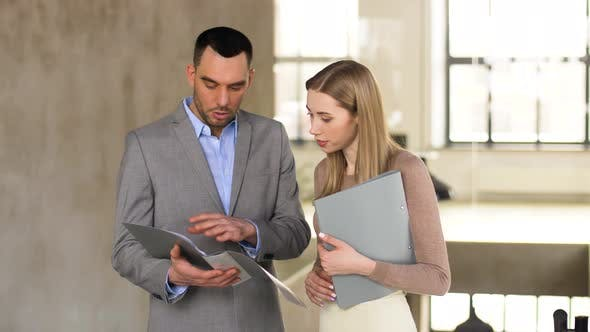 Thumbnail for Businesswoman and Businessman Discussing Folder