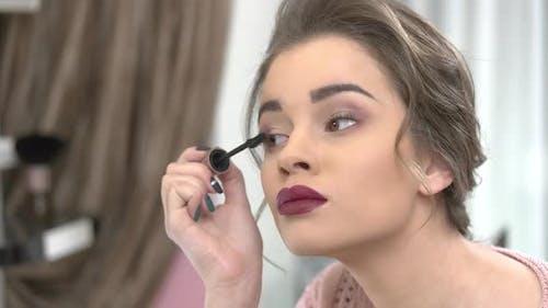 Young Woman Using Eyelash Brush