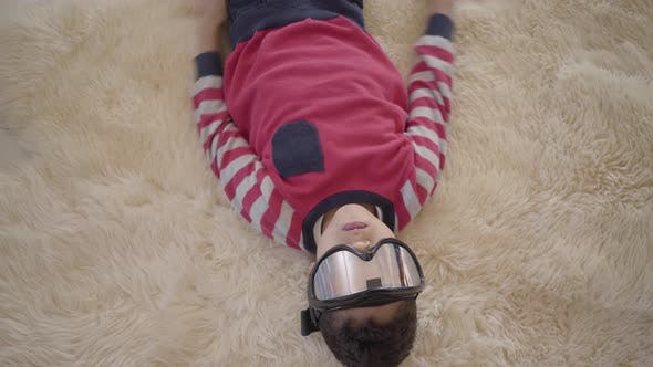 Cover Image for Portrait of Adorable African American Boy Lying on the Floor on the Beige Fluffy Carpet with Ski