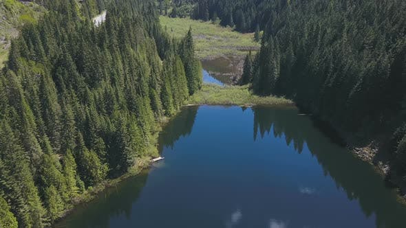 Thumbnail for Aerial Drone Of A Lake And Valley With Reflections Of Evergreen Trees On A Mountain 2