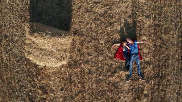 Top View of Dad and Son Superheroes Lying on Field