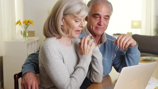 Thumbnail for Happy mature couple using laptop computer to pay bills