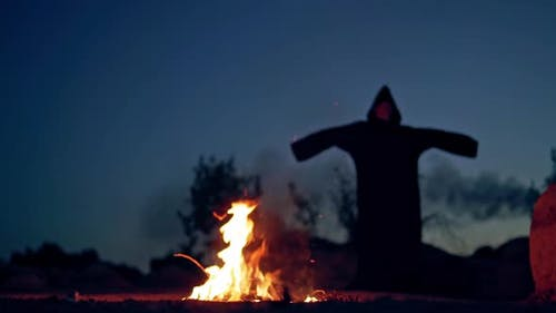 Concept of Halloween and witchcraft. Black witch in a mantle stays in front of fire