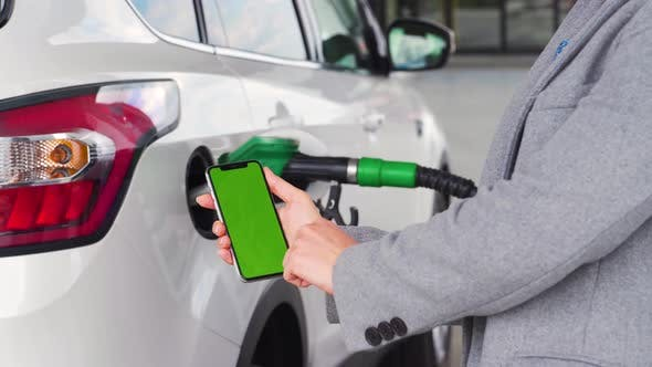Thumbnail for Woman Uses a Mobile Application in a Smartphone To Pay for Refueling a Car. Smartphone with a Green